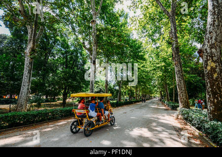Seville, Spain - July 15, 2018: Family rides on a cycle tour bike on a path at Maria Luisa park in the summer - Stock Photo