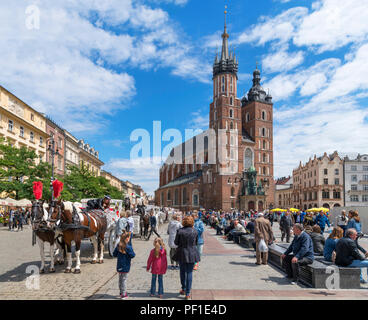 Krakow Old Town. Horse and carriage in front of St Mary's Basilica in the Main Square ( Rynek Główny ), Kraków, Poland - Stock Photo