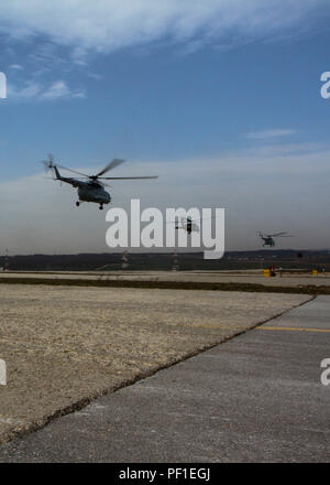 Flight crews from Croatia, Slovenia, Switzerland and the United States take off from Camp Bondsteel, Kosovo during a two-day, multi-ship aviation exercise held to test the multinational crews' ability to operate as one team and communicate with each other while in flight, Feb. 23, 2016. The exercise was run by members of the Connecticut National Guard's 1st Battalion, 169th Aviation Regiment in order to train the Soldiers who will take their place in Kosovo: the Arizona National Guard's 2-285th Assault Helicopter Battalion. The current rotation of National Guard and U.S. Army Reserve Soldiers  - Stock Photo