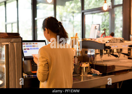 Woman at the cash register takes orders and bills using modern c