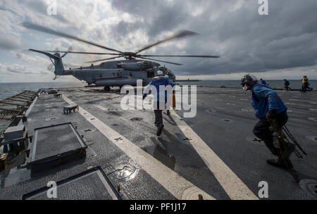 160308-N-VS214-220 EAST SEA (March 9, 2016) Members of the flight deck crew on board dock landing ship USS Harpers Ferry (LSD 49) move in to secure a CH-53 Sea Stallion attached to Marine Medium Tilt Rotor Squadron (VMM) 166 (Reinforced) to the flight deck. USS Harpers Ferry is assigned to the Boxer Amphibious Ready Group and is participating in exercise Ssang Yong 16. Ssang Yong is a biennial combined amphibious exercise conducted by forward-deployed U.S. forces with the Republic of Korea Navy and Marine Corps, Australian Army and Royal New Zealand Army Forces in order to strengthen our inter - Stock Photo