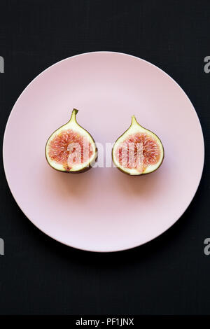 Two halves of fresh fig on pink plate over black background, view from above. Flat lay, overhead, top view. - Stock Photo