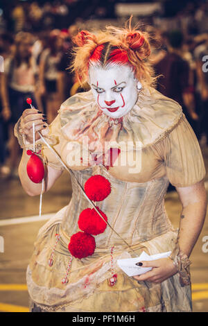 A female cosplayer dressed as Pennywise the clown from Stephen King's November IT and looking evil and menacing at a comic con event - Stock Photo