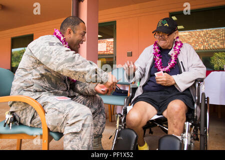 Retired U.S. Army veteran S. Wilcox (right) and U.S. Air Force Tech Sgt. Manuel Orantes from the 647th civil engineering squadron, play a hand of cards during the National Salute to Hospitalized Veterans, Feb. 23, 2016, aboard Tripler Army Medical Center, in Honolulu. This annual event allows people to visit and recognize veterans for their military service. (U.S. Marine Corps photo by Cpl. Jonathan E. LopezCruet) - Stock Photo