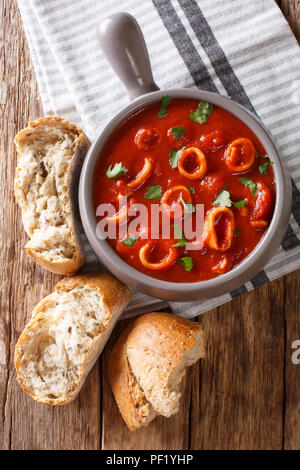 Italian thick tomato soup with squids close-up in a bowl, served with bread. vertical top view from above - Stock Photo