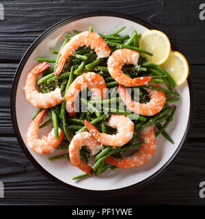 Delicious shrimp salad with green beans, cheese and lemon close-up on a plate on the table. top view from above - Stock Photo