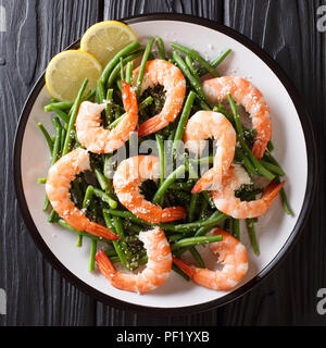 seafood shrimp salad with green beans, cheese and lemon close-up on a plate on a table. top view from above - Stock Photo
