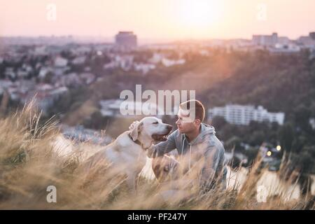 Morning walk with dog. Young man and his labrador retriever on the meadow against city at sunrise. - Stock Photo