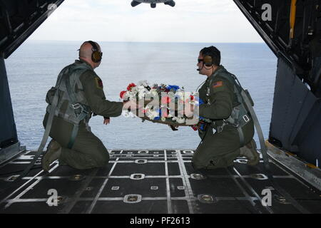 From left, Tech. Sgt. Brett Bollinger and Tech. Sgt. Michael Gillette, both loadmasters at the 1st Special Operations Squadron prepare to drop a wreath from an MC-130H Combat Talon II off the coast of the Philippines Feb. 26, 2016 in memory of those who died in the crash of Stray 59.  The flight honors those who were lost 35 years ago when a 1st SOS MC-130E, call sign STRAY 59, crashed during an exercise killing eight crew members and 15 passengers. (U.S. Air Force photo by Master Sgt. Kristine Dreyer, 353rd SOG PA/Released) - Stock Photo