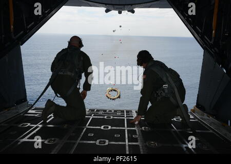 From left, Tech. Sgt. Brett Bollinger and Tech. Sgt. Michael Gillette, both loadmasters at the 1st Special Operations Squadron drop a wreath from a U.S. Air Force MC-130H Combat Talon II off the coast of the Philippines Feb. 26, 2016 in memory of those who died in the crash of Stray 59. The flight honors those who were lost 35 years ago when a 1st SOS MC-130E, call sign STRAY 59, crashed during an exercise killing eight crew members and 15 passengers. (U.S. Air Force photo by Master Sgt. Kristine Dreyer, 353rd SOG PA/Released) - Stock Photo