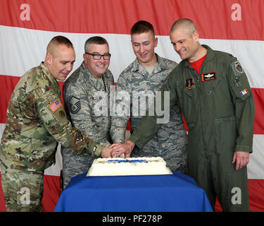 Cutting the cake at the 75th anniversary of the 132nd Wing are (from left to right) Maj. Gen. Tim Orr, adjutant general of the Iowa National Guard, Master Sgt. Don Worrell, Airman 1st Class Justin Hopp, and Col. Shawn Ford, 132nd Wing commander. Worrell and Hopp continued an age-old military tradition of the oldest and youngest service member cutting their branch's cake, with Worrell representing the oldest Airman in the Wing, and Hopp the youngest. (Iowa National Guard photo by Staff Sgt. Chad D. Nelson) - Stock Photo