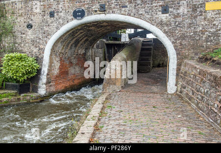 The Staffordshire and Worcestershire Canal near Penkridge showing water coming out between the opening lock gates above. - Stock Photo