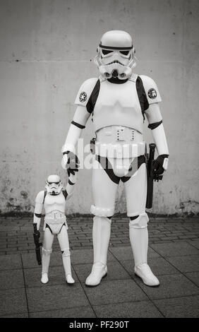 A male cosplayer dressed as a Stormtrooper from the Star Wars franchise and holding the hand of his Stormtrooper son in a comic con family portrait - Stock Photo