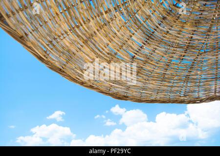 Beach Straw Umbrella with Clear Blue Sky on Sunny Summer Day. Beach Umbrella Wallpaper Background. - Stock Photo