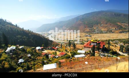 Aerial view of Paro Dzong or Rinpung Dzong, a buddhist monastery and fortress on the hill above a river Paro Chu , Bhutan. - Stock Photo