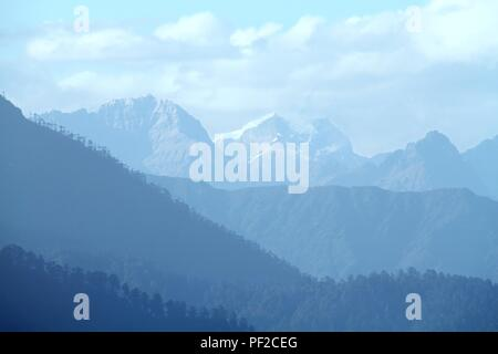 Morning mountain landscape with layer of mountain peaks covered with coniferous deciduous forests. View from Dochula Pass on the road from Thimphu to  - Stock Photo
