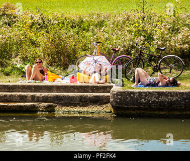 Girls women and young ladies with their bikes cycles sunbathing on the banks of the river Thames under a parasol umbrella during the heatwave of 2018 - Stock Photo