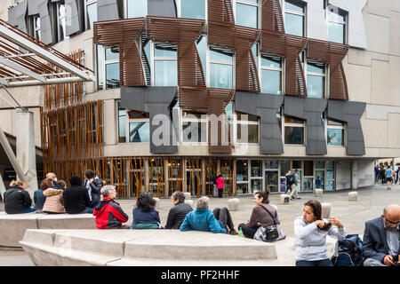 Tourists and visitors relaxing outside the Scottish Parliament building in Edinburgh, Scotland. - Stock Photo