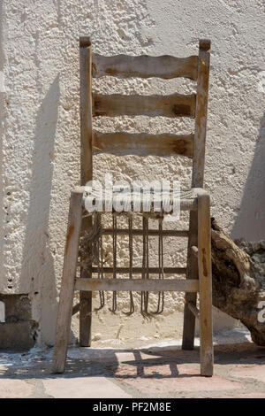 a rickety old worn out antique chair with a wicker seat. - Stock Photo