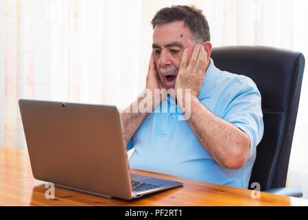 Surprised Senior man working with laptop. - Stock Photo