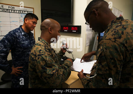 """MARINE CORPS BASE HAWAII – (From left to right) Navy Air Controlman Petty Officer 2nd Class Rodrigo Benavides, a flight planner with Marine Corps Air Station Kaneohe Bay, and a Los Angeles native; Cpl. Brandon Stallworth, a flight planner with MCAS, and a Detroit native; and Cpl. Khiry Wright, a flight planner with MCAS, go over various aircraft's estimated time of departure, Feb. 11, 2016. After going on boards for """"Marine of the Quarter"""" and meritorious corporal, Wright, a New York City native, was awarded the title """"Marine of the Year"""" for his commitment to improving himself and those aroun - Stock Photo"""