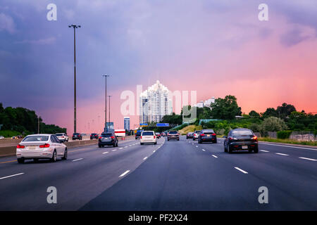 Night traffic. Cars on highway road at sunset evening in typical busy american city. Beautiful amazing night urban view with red, yellow and blue sky  - Stock Photo