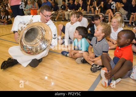 170920-N-KB426-084  OKLAHOMA CITY (Sept. 20, 2017) Musician 3rd Class Zachary Buckwash, assigned to Navy Band Southeast's Brass Quintet, left, interacts with students at St. Eugene's Catholic School during a community relations event as part of Navy Week Oklahoma City. Navy Week programs serve as the principal outreach effort into areas of the country without a significant Navy presence, helping Americans understand that their Navy is deployed around the world, around the clock, ready to defend America at all times. (U.S. Navy photo by Mass Communication Specialist 2nd Class James Vazquez/Rele - Stock Photo