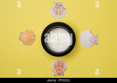 Diwali candle surrounded by four sea shells against light yellow background - Stock Photo