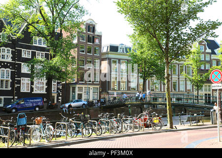 AMSTERDAM, NETHERLANDS - JUNE 6, 2018: beautiful view of Amsterdam canals with parked bikes, people on the bridge and typical dutch houses - Stock Photo