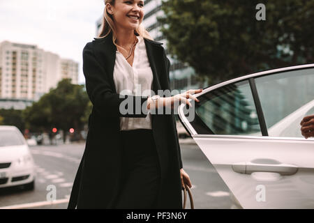 Smiling woman commuter getting out of a taxi. Businesswoman getting off a cab. - Stock Photo