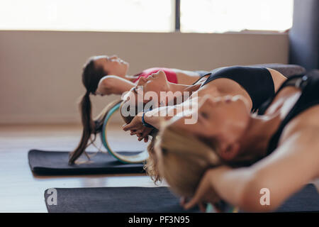 Fitness women lying on yoga and pilates wheel at a gym. Women doing back stretching workout holding their heads. - Stock Photo