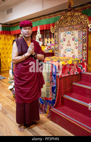 Posed portrait of a Buddhist monk from Bhutan with his hands clasped at a ceremony in Woodside, Queens, New York City. Is he wearing an apple watch? - Stock Photo