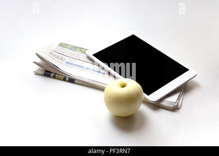 Digital tablet, folded newspaper and ripe apple on white background - Stock Photo