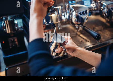 Male barista prepares beverage on coffee machine in cafe. Professional espresso preparation by barman - Stock Photo