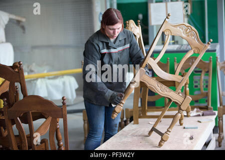 Belarus, the city of Gomel, on April 26, 2018. A factory for processing wood and making chairs. Working at the factory makes a chair. Making expensive - Stock Photo