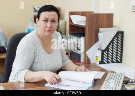 Belarus, Gomel, 25 April 2018. The office is central. Woman office worker at work desk.Russian bureaucracy - Stock Photo