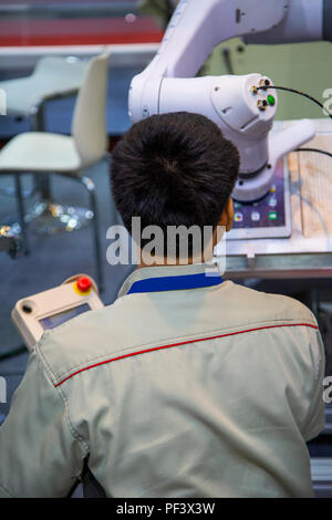 Worker control robot arm to loadind and un loading tablet - Stock Photo