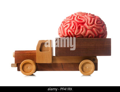 Wooden truck carries a rubber brain, metaphor for brain drain. - Stock Photo