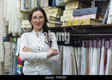 Portrait of happy woman owner with crossed arms in interior fabrics store, background fabric samples. Small business home textile shop - Stock Photo