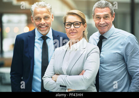 Group of smiling mature corporate colleagues standing confidently together in the lobby of a modern office building - Stock Photo