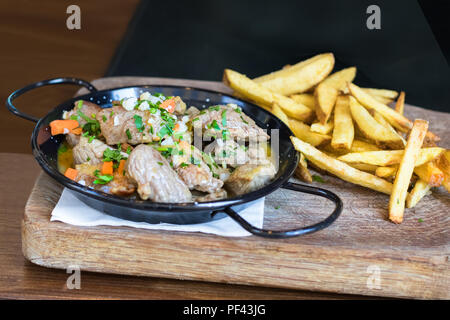 A pan with meat, souce and vegetables accompanied with french fries potatoes on a wooden table. - Stock Photo