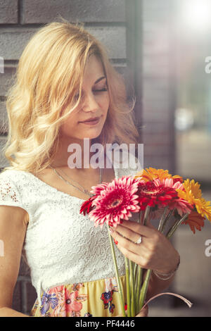 pensive young blond woman with bouquet of flowers looking at camera - Stock Photo
