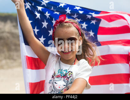 A little smiling patriotic girl holds an American flag celebrating National holiday Independence Day USA on July 4 - Stock Photo
