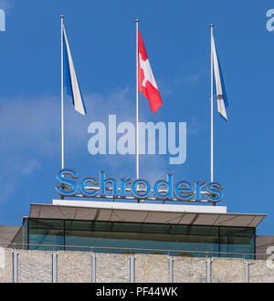 Zurich, Switzerland - September 27, 2017: upper part of a building bearing the sign of the Schroders company and flags of Zurich and Switzerland. Schr - Stock Photo