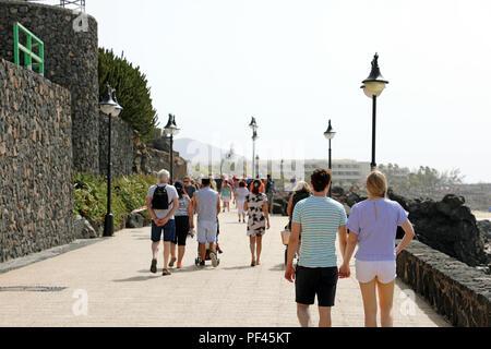 LANZAROTE, SPAIN - APRIL 18, 2018: Tourists walking on Playa Blanca promenade, Lanzarote, Canary Islands, Spain - Stock Photo