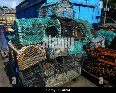 Some of the creels, lobster pots and other fishing paraphernalia stacked up on the pier at the small fishing village of Tarbert, Loch Fyne in Scotland. - Stock Photo