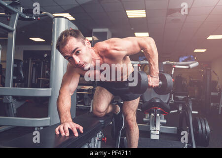 Sportsman doing dumbbell rows on bench at gym. - Stock Photo