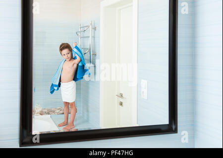 adorable healthy child dry off his body with blue towel in morning bathroom - Stock Photo