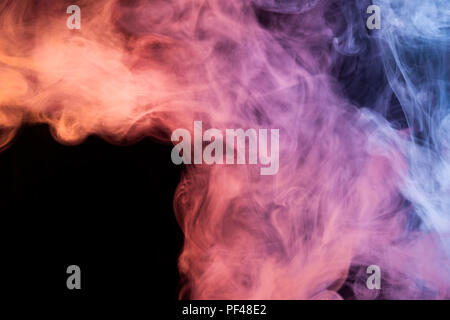 Thick red, pink and blue smoke on a black isolated background. Background from the smoke of vape - Stock Photo