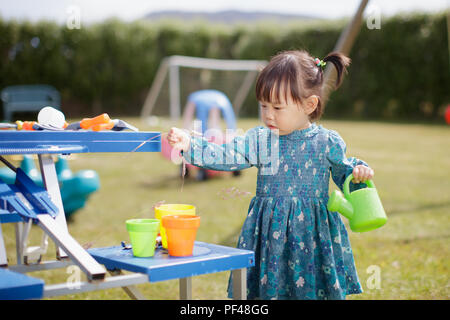 baby girl  pretend play in Summer garden - Stock Photo